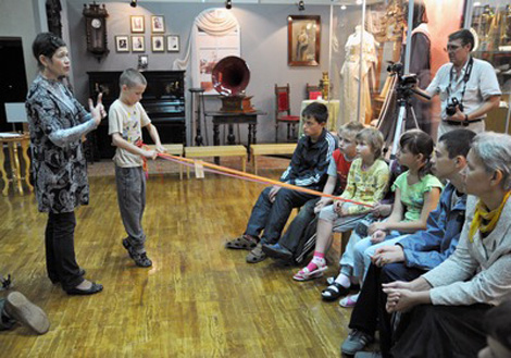 Марина Згинникова учит детей ткать пояс на бёрдышке